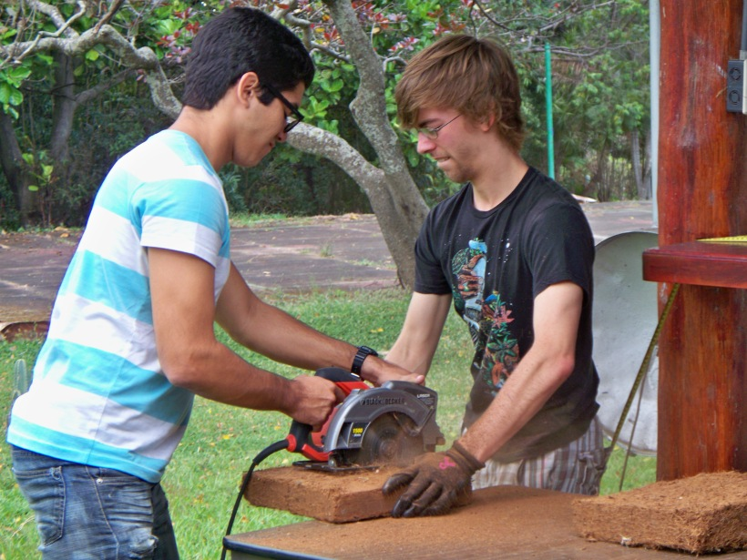 Hugo and Robbi practicing safe saw use to cut the coconut fiber